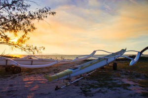 Outrigger canoes at sunset.
